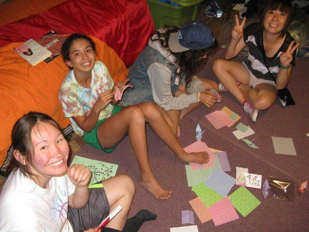Tomoha, from Japan (right) teach her cabin mates how to make origami paper cranes.  From left - Naomi, from Crow Nation; Devi, from Maryland, Maryland; Saja, from Libya; Tomoha, from Japan