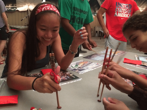 Maddie, from Virginia, practices her chopsticks skills.