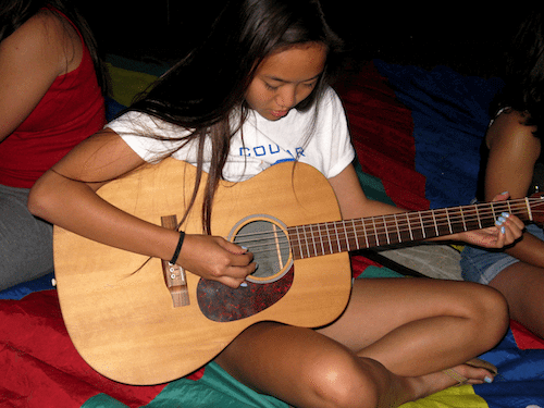 Maddie works on pairing guitar chords to the lyrics of her song during a group songwriting session of the Arts and Human Rights workshop